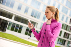 Checking pulse. Young woman timing her pulse with her phone stock photos