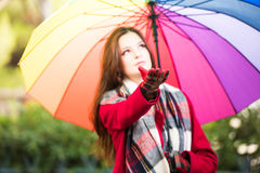 Checking for rain. Beautiful young girl taking a midday walk through a city park wearing a bright red coat with a colorful umbrella checking for an early rain Royalty Free Stock Photo