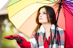 Checking for rain. Beautiful young girl taking a midday walk through a city park wearing a bright red coat with a colorful umbrella checking for an early rain Stock Photo