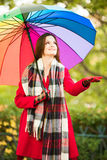 Checking for rain. Beautiful young smiling girl taking a midday walk through a city park wearing a bright red coat with a colorful umbrella checking for an early Stock Images