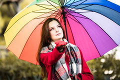 Checking for rain. Beautiful young smiling girl taking a midday walk through a city park wearing a bright red coat with a colorful umbrella checking for an early Royalty Free Stock Image