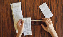 Checking Receipts the Hard Way. Checking receipts with Abacus on wood table Royalty Free Stock Photos