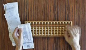 Checking Receipts the Hard Way. Checking receipts with Abacus on wood table Stock Images