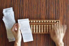Checking Receipts the Hard Way. Checking receipts with Abacus on wood table Stock Photos