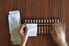 Checking Receipts the Hard Way. Checking receipts with Abacus on wood table Royalty Free Stock Images