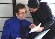 Checking reports. Businessman and woman checking financial reports Royalty Free Stock Photography