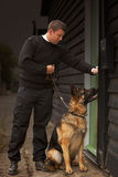 Checking Security. A security guard/dog handler checking security at a factory or trading estate Stock Image