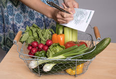 CHECKING A SHOPPING LIST AGAINST A BASKET OF SALAD Stock Photography