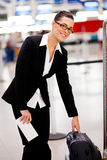 Checking size of luggage at airport. Businesswoman checking size of her carry-on luggage at airport Stock Images