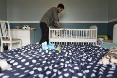 Checking on sleeping baby Stock Image