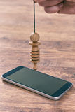 Checking smart phone with pendulum Royalty Free Stock Images