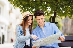 Checking some information in the guidebook. Couple sitting on bench and looking in map in new city. Checking some information in the guidebook of city royalty free stock image