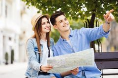 Checking some information in the guidebook. Couple sitting on bench and looking in map in new city. Checking some information in the guidebook of city stock photography