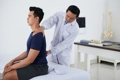 Checking spine. Osteopath checking spine of sitting young Vietnamese man stock image