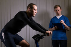 Checking the strength capabilities. Sportsman is sitting o a stationary bike and the doctor is supervising him royalty free stock images