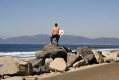 Checking the surf. A young man stands on the coastline and checks surf conditions Royalty Free Stock Images