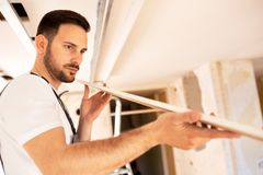 Checking the surface smoothness of a ceiling element royalty free stock image