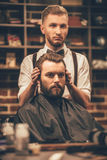 Checking symmetry. Hairdresser checking symmetry of haircut of his client at barbershop Royalty Free Stock Photography
