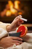 Checking temperature on thermometer. Checking temperature, illness, winter cold, female hands holding tea mug with blood orange and thermometer in front of Royalty Free Stock Photo