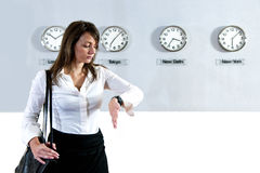 Checking the time. Young business woman checking the time on her watch with various international clocks, displaying world time, in the background Stock Photo