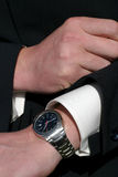 Checking the time. Business man checking the time on his wrist watch Stock Photos