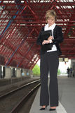 Checking the time. Pretty blond businesswoman standing on the trainstation checking her watch to see when the next train will arrive Royalty Free Stock Photos