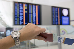 Checking time for boarding. Hand hold a passport, transit pass and ticket checking time to depart Royalty Free Stock Photos