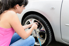 Checking Tire Pressure. Young woman checking pressure and inflating car tires Stock Image