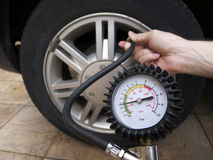 Checking Tire Pressure. Close-up of manometer and man hands checking tyre pressure with gauge Royalty Free Stock Photo