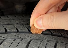 Checking tire tread depth/wear with a penny. An old trick to checking a tire`s tread depth and wear is to use a penny with Abraham Lincoln`s head Royalty Free Stock Images