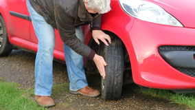 Checking tire or tyre tread on a motor vehicle. stock footage