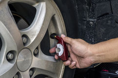 Checking tires with a hand held tire pressure gauge. Stock Image