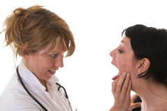 Checking the tonsils. Female doctor checking out the tonsils of her patient royalty free stock images