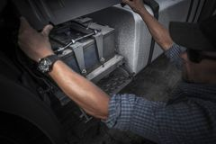 Checking on Truck Battery. Trucking Concept Photo. Caucasian Truck Driver Opening Vehicle Battery Compartment Royalty Free Stock Images