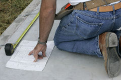 Checking it Twice. Contractor referring to build plans to verify measurements Royalty Free Stock Photo