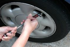 Checking tyre pressure Royalty Free Stock Image