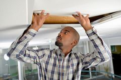 Checking under ceiling panel. Checking under a ceiling panel Stock Photos