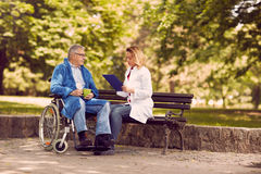 Checking up the history of the disease senior patient in wheelch. Nurse checking up the history of the disease senior patient in wheelchair Stock Photography