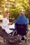 Checking up the history of the patient in wheelchair. Nurse checking up the history of the patient in wheelchair Royalty Free Stock Photos