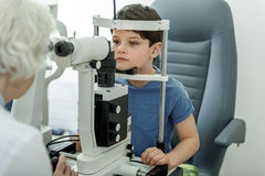 Checking vision of little kid. Small boy is seriously looking ahead. He putting his head into optic equipment in order to verify sight. Portrait Stock Images