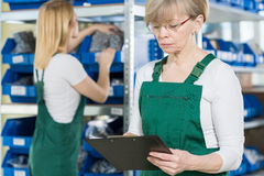 Checking the warehouse. Working women checking the warehouse in big factory Stock Photo