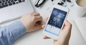 Checking wather using smartphone app. Snowy and cold stock footage