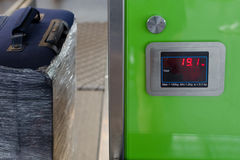 Checking the weight of luggage in the airport. During the check-in by low cost airlines restrictions. Wrapping baggage before travel by airplane. Suitcase in Royalty Free Stock Photography