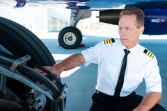 Checking the wheels. Confident male pilot in uniform examining an airplane wheels Stock Images