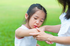 Checking wound. Mother checking wound to her daughter at outdoor park royalty free stock images