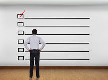 Checklist. Businessman in office looking at wall with checklist concept Stock Photography