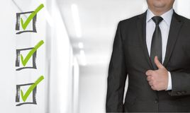 Checklist concept and businessman with thumbs up royalty free stock image