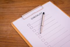 Checklist concept - checklist, paper and a pen with checklist word on wooden table.  stock photos