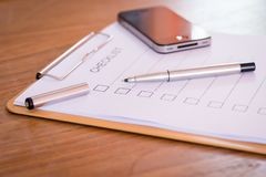 Checklist concept - checklist, paper and a pen with checklist word on wooden table.  royalty free stock images