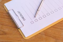 Checklist concept - checklist, paper and a pen with checklist word on wooden table.  royalty free stock photos